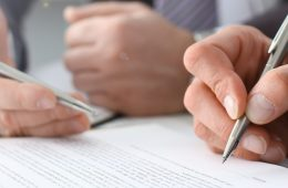 Male arm in suit and tie fill form clipped pad with silver pen closeup. Sign gesture read pact sale agent bank job make note loan credit mortgage investment finance executive chief legal teamwork law